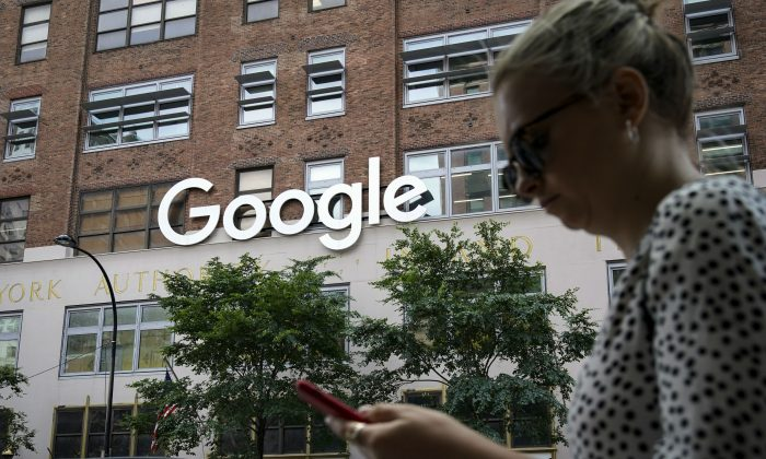A woman looks at her smartphone as she walks past Google Building 8510 at 85 10th Ave., New York City, N.Y., on June 3, 2019.