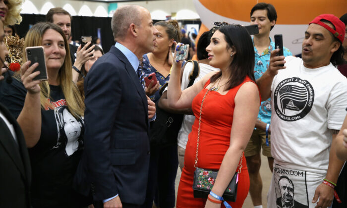 Laura Loomer, second from left, holds up a phone at an event in Los Angeles, Calif., in an Oct. 20, 2018,
