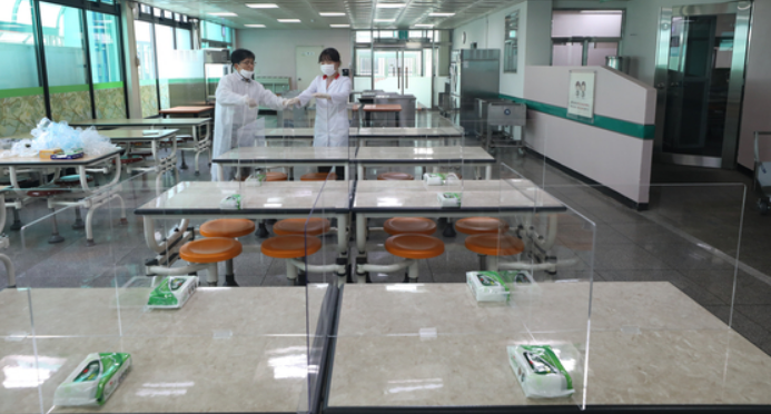 Teachers set up dividers on lunch tables at a high school in western Seoul on Monday,