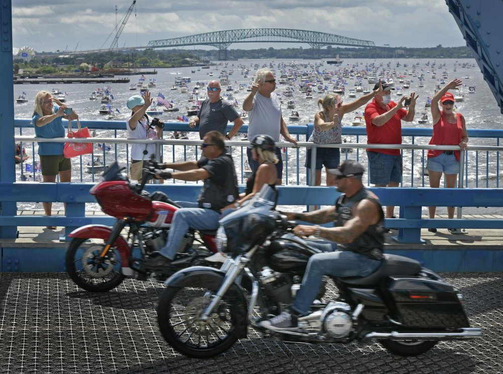 Supporters of President Donald Trump wave at motorcycles coming over the Main Street Bridge as hundreds of boats idle under the downtown bridge on the St. Johns River during a rally Sunday, June 14, 2020, in Jacksonville, Fla., celebrating Trump's birthday.