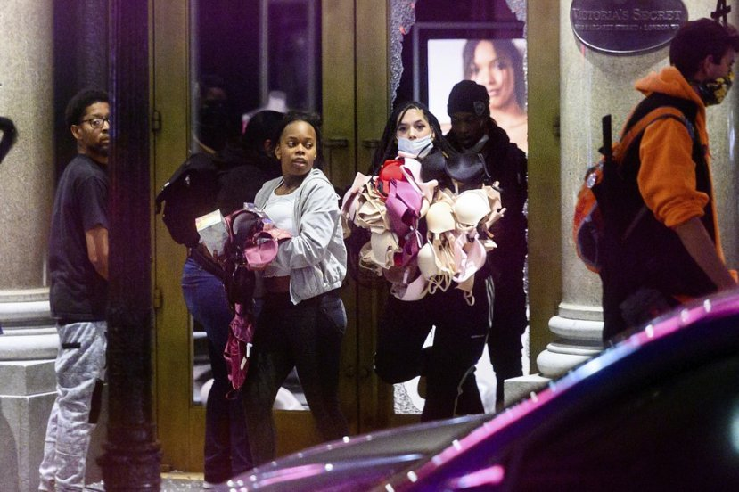 FILE - In this May 30, 2020, file photo, women carry merchandise from a Union Square Victoria's Secret store in San Francisco. Police say many of the smash-and-grab thefts have been carried out by caravans of well-coordinated criminals,