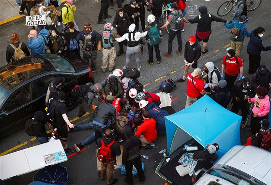 Medics tend to a man who was shot in the arm by a driver of a black vehicle at a protest against racial inequality in Seattle, Washington, on Sunday.