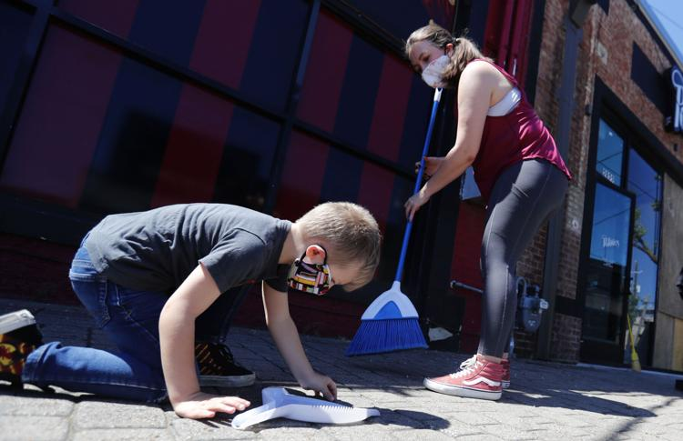 Harry Verhover, 4, helps his mother Alexis Verhover pick up the last bits of broken glass as they volunteered to clean up after a night of protests Saturday, May 30, 2020, in Dallas. Protests escalated over the death of George Floyd who died after being restrained by Minneapolis police officers on Memorial Day.  LM Otero / AP