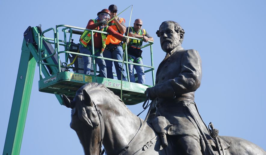 An inspection crew from the Virginia Department of General Services takes measurements as they inspect the statue of Confederate Gen. Robert E. Lee on Monument Avenue Monday, June 8, 2020, in Richmond, Va. Virginia Gov. Ralph Northam has ordered the removal of the statue.
