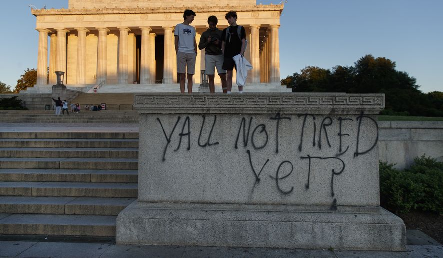 "Spray paint that reads ""Yall Not Tired Yet?"" is seen on the base fo the Lincoln Memorial on the National Mall in Washington, early Sunday, May 31, 2020,"