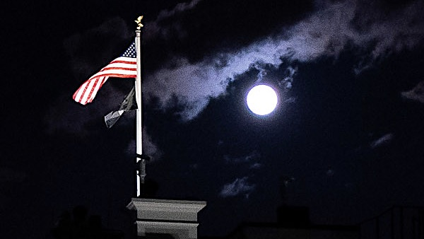The Full Pink Moon, the largest full moon of 2020, rises above the North Portico of the White House Tuesday, April 7, 2020, in Washington, D.C.