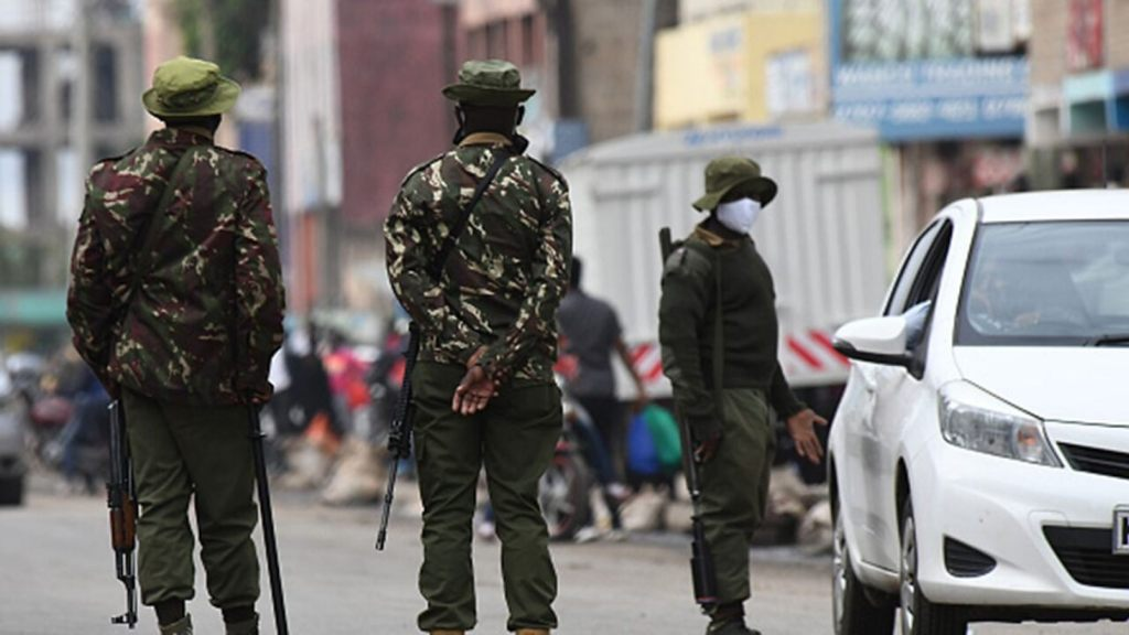 Kenyan police officers inspects the identification of a resident at a checkpoint in Eastleigh, Nairobi, on May 7, 2020,