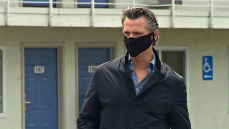 Gov. Gavin Newsom walks outside a Santa Clara County motel set to shelter homeless people amid the coronavirus pandemic ahead of a briefing on April 18, 2020.