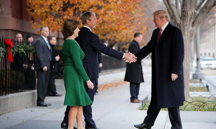 Former first lady Laura Bush and former President George W. Bush greet President Donald Trump outside of Blair House in Washington on Dec. 4, 2018.