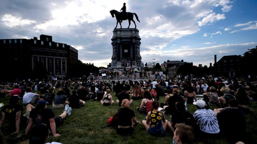 Protesters sit near the statue of Robert E. Lee on Monument Avenue in Richmond, Va., Wednesday, June 3, 2020.