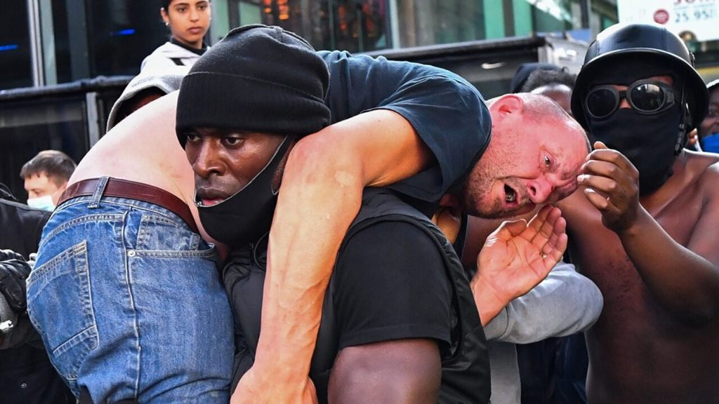 A protester carries an injured counterprotester to safety, near the Waterloo station during a Black Lives Matter protest in London, Britain, June 13, 2020.