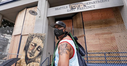 """Rodney Maine displays his new """"Black Lives Matter"""" tattoo after asking a passerby to take his photo in front of a plywood-covered and fenced-off Seattle police precinct Tuesday, June 9, 2020, in Seattle."""