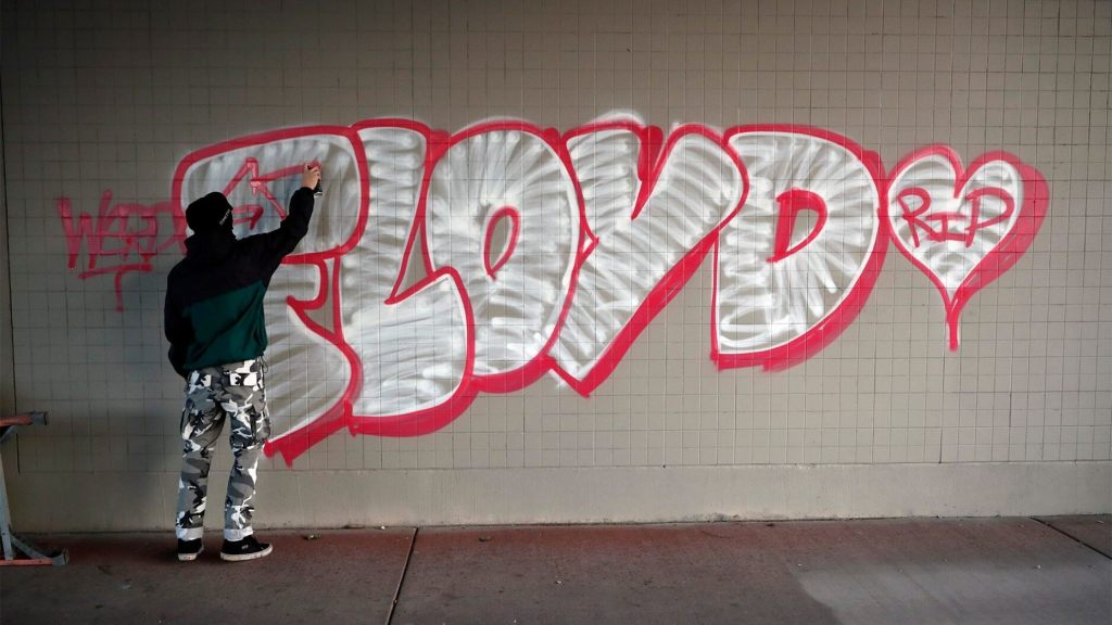 A protester spray paints George Floyd's name Friday, May 29, 2020,