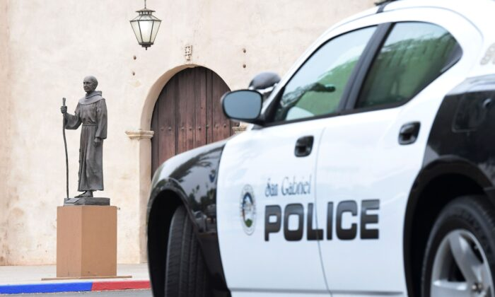 A police vehicle is seen parkned near a statue of Father Junipero Serra in front of the San Gabriel Mission in San Gabriel, California on June 21, 2020.