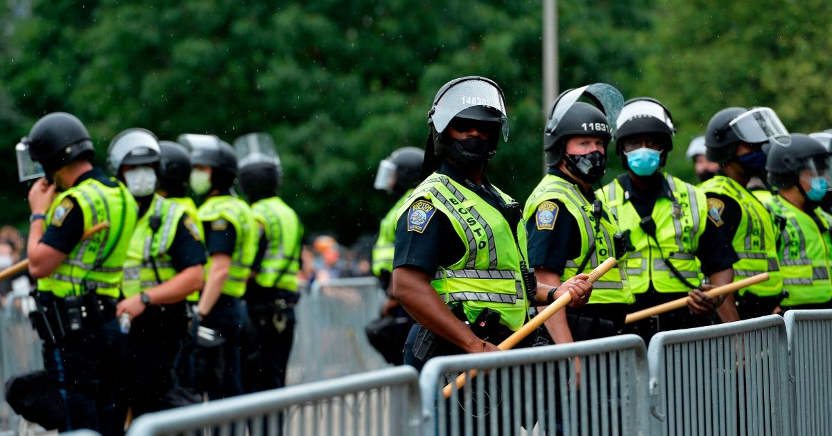 Police officers in riot gear stand guard outside the State House in Boston on June 27, 2020