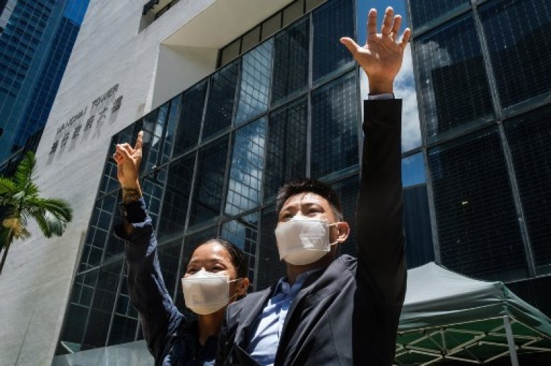 Elaine To (L), 41, and Henry Tong, 39, celebrate outside the District Court in Hong Kong after the couple were found not guilty of rioting during the widespread pro-democracy protests in 2019.