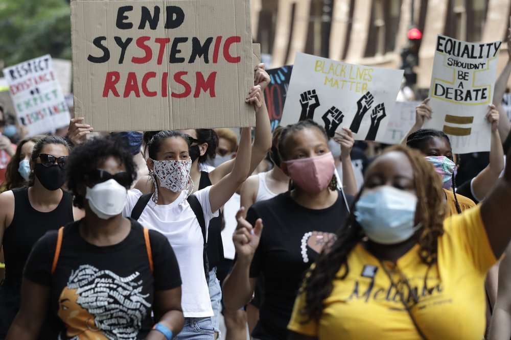 FILE - In this June 19, 2020, file photo, people demonstrate in Chicago,