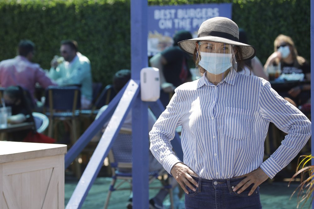 A hostess waits to sit customers on a restaurant at the pier Sunday, July 12, 2020, in Santa Monica, Calif.