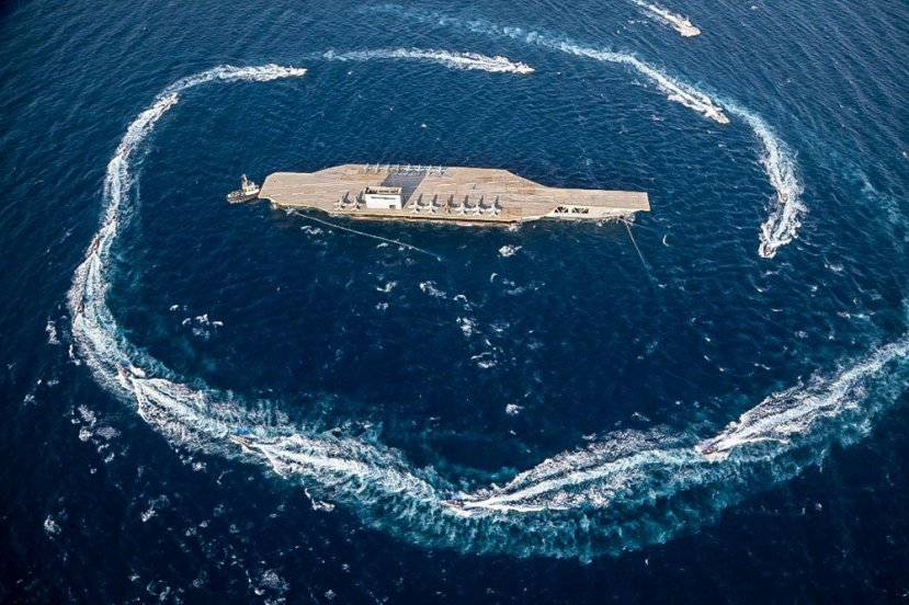 In this photo released Tuesday, July 28, 2020, by Sepahnews, Revolutionary Guard's speed boats circle around a replica aircraft carrier during a military exercise.