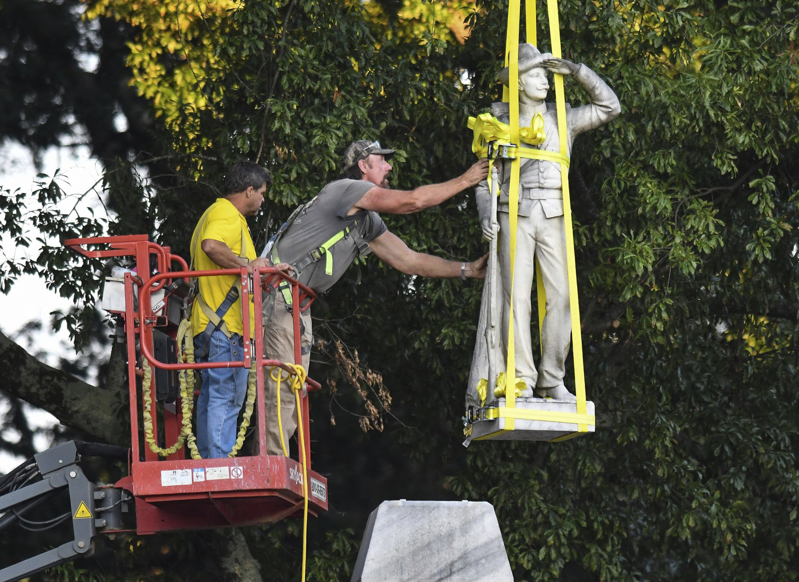 The Confederate statue located in the Circle at the University of Mississippi is lowered to the ground as part of the process to move it to the Confederate Soldiers Cemetery on campus, in Oxford, Miss. Tuesday, July 14, 2020.
