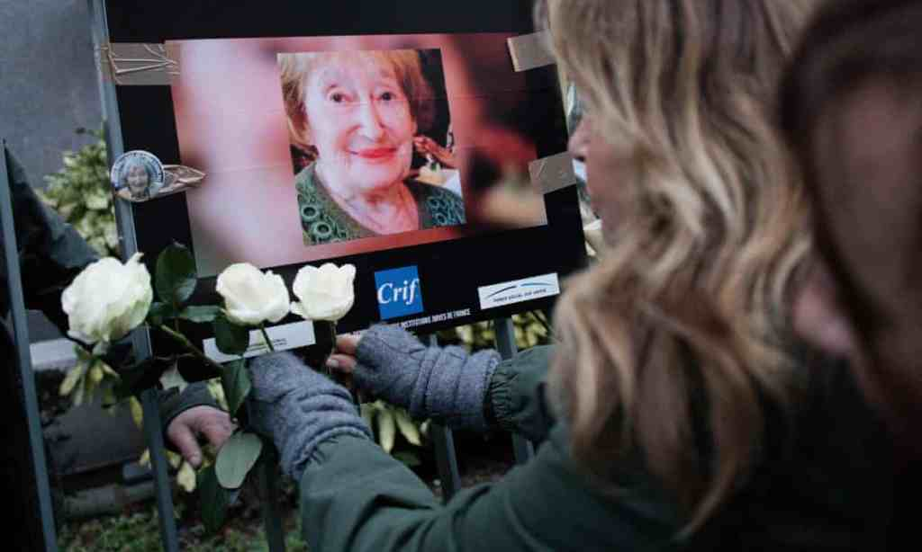 A woman pays tribute to Mireille Knoll outside her home in Paris ,