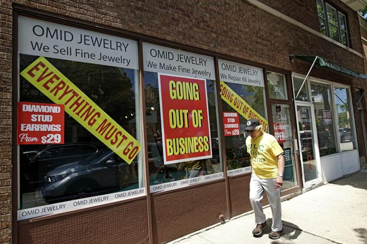A man walks past a retail store that is going out of business due to the coronavirus pandemic in Winnetka, Ill., Tuesday, June 23, 2020.