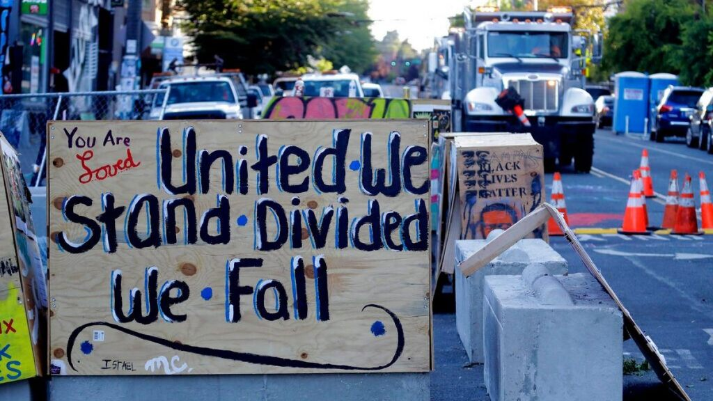 "A sign on a barricade reads ""United we stand divided we fall,"" as a truck and other heavy equipment from the Seattle Department of Transportation is staged at the CHOP ,"