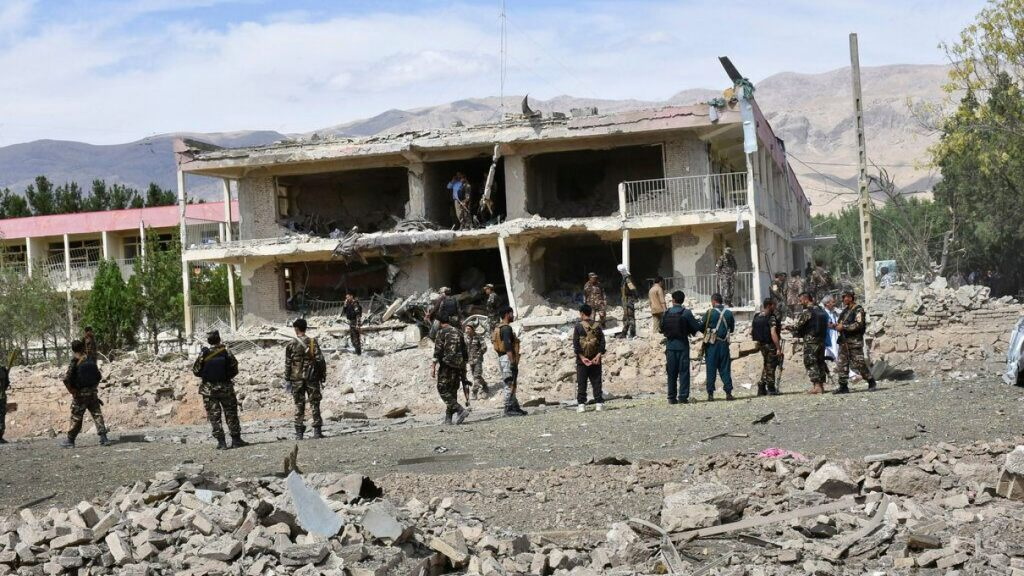 Afghan security personnel inspect the site of a car bomb blast,