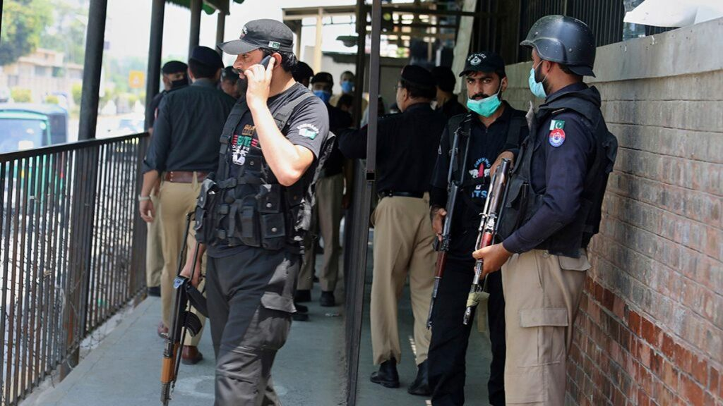 Police officers gather at an entry gate of district court following the killing of Tahir Ahmad Naseem, who was in court accused of insulting Islam, in Peshawar, Pakistan, Wednesday, July 29, 2020.