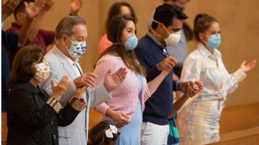 Family members hold hands as they pray at the first English Mass with faithful present at the Cathedral of Our Lady of the Angels in downtown Los Angeles,
