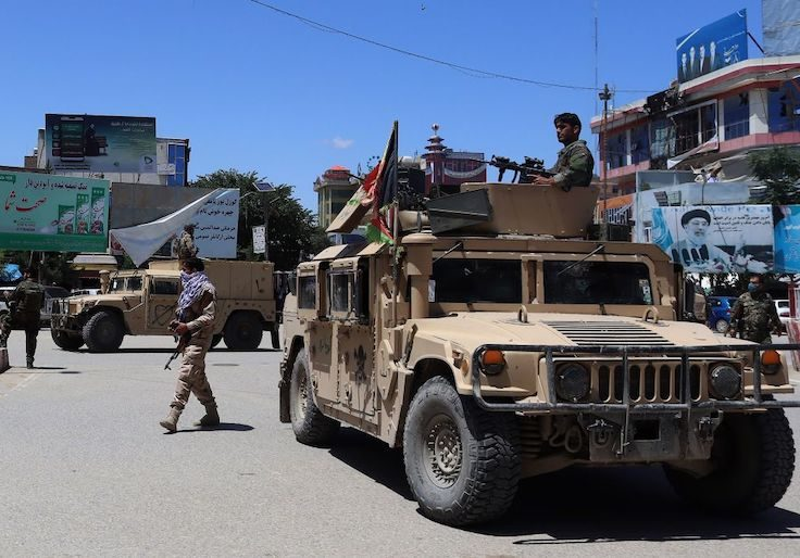 Afghan security forces sit in a Humvee amid ongoing fighting with Taliban militants,