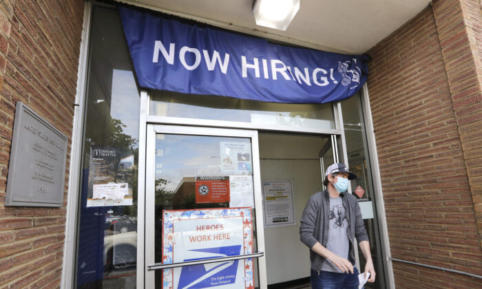 A customer walks out of a U.S. Post Office branch and under a banner advertising a job opening, in Seattle, Wash., on June 4, 2020.