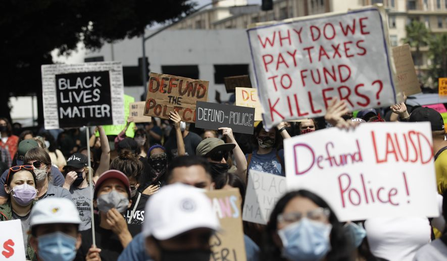 Demonstrators holds signs during a protest to demand the defunding of the Los Angeles school district police outside of the school board headquarters Tuesday,