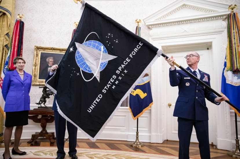 Gen. Jay Raymond (R), Chief of Space Operations, and CMSgt Roger Towberman (L), with Secretary of the Air Force Barbara Barrett present President Donald Trump with the official flag of the United States Space Force in the Oval Office at the White House in Washington, D.C.,