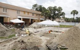 Archaeologists work to uncover graves at the former site of the Zion cemetery found underneath the Robles Park Village housing complex ,