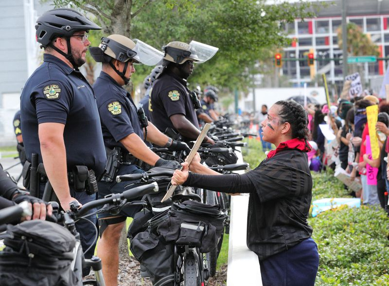 A protestor holds up a sign in front of Orlando Police officers lined up in front of OPD headquarters on June 2, 2020.