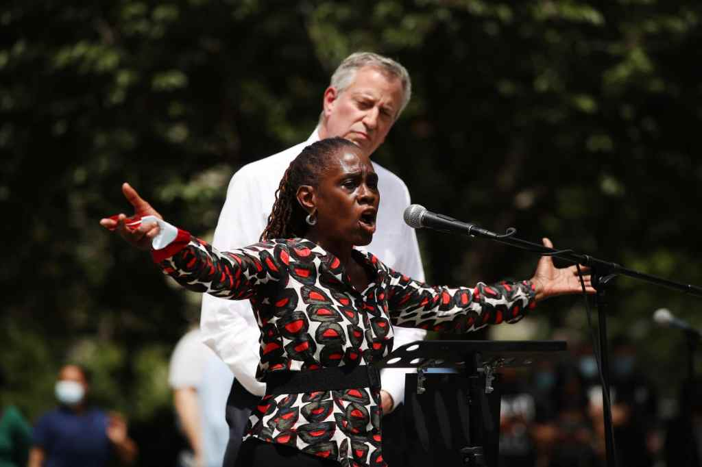 New York Mayor Bill de Blasio listens as his wife, First Lady Chirlane McCray, speaks to an estimated 10,000 people as they gather,