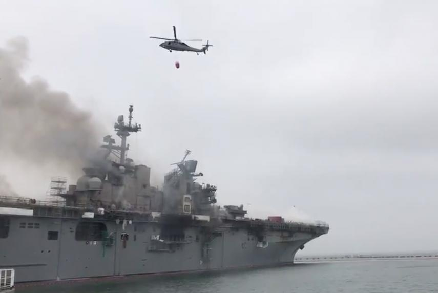 U.S. Navy helicopters assist in fighting a fire that has been burning on the SS Bonhomme Richard since Sunday morning.