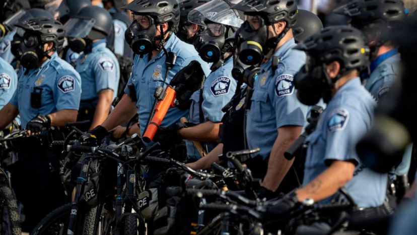 FILE - In this May 27, 2020, file photo, police gather en masse as protests continue at the Minneapolis 3rd Police Precinct in Minneapolis.