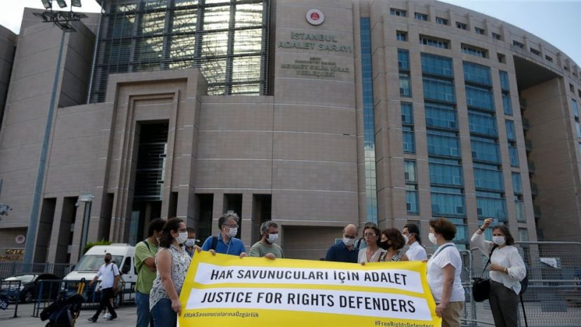 Protesters from Amnesty International stage a protest outside a court in Istanbul, Friday, July 3, 2020, where the trial of 11 prominent human rights activists for terror-related charges and adjourned proceedings was continuing.