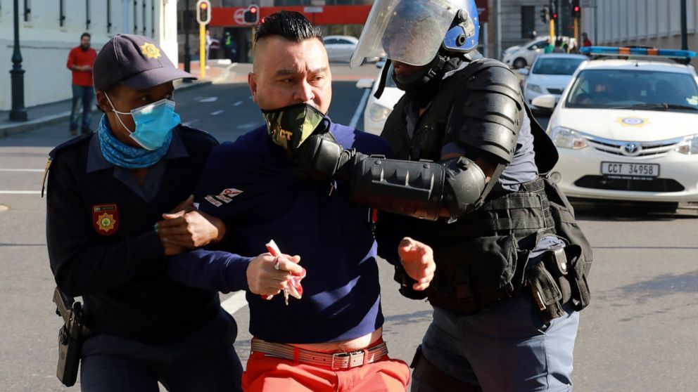 A demonstrator working in the hospitality industry is arrested by police during a protest against lockdown regulations in the streets close to Parliament in Cape Town, South Africa, Friday July 24, 2020. People from various hospitality or restaurant establishments marched on parliament to raise awareness about the industry's declining revenues amid the Covid-19 lockdown.