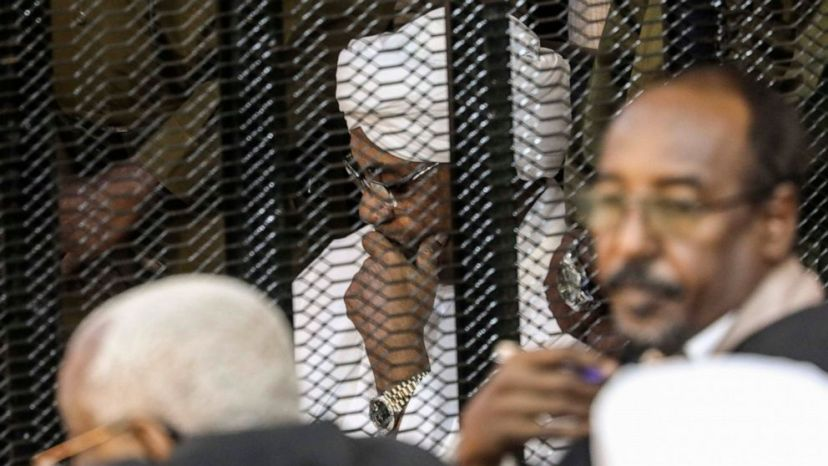 FILE - In this Aug. 24, 2019 file photo, Sudan's autocratic former President Omar al-Bashir sits in a cage during his trial on corruption and money laundering charges,