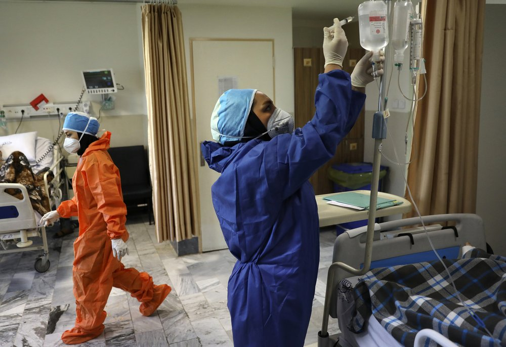 FILE - In this June 16, 2020, file photo, nurses tend to COVID-19 patients at the Shohadaye Tajrish Hospital in Tehran, Iran. Iran surpassed 20,000 confirmed deaths from the coronavirus on Wednesday, Aug. 19, 2020, the health ministry said, the highest death toll for any Middle East country so far in the pandemic.