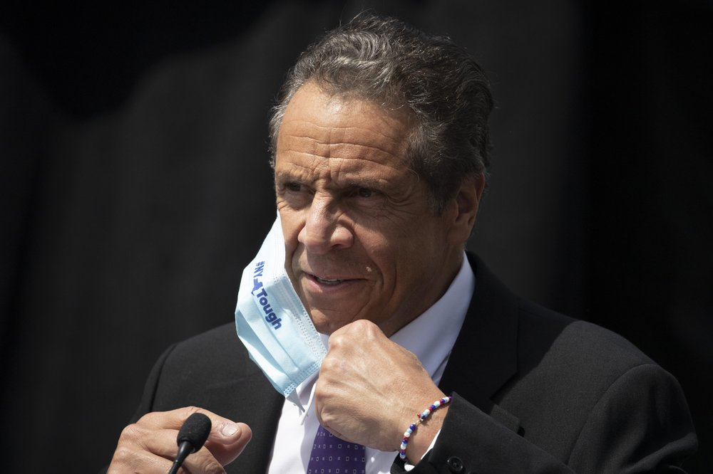 FILE - In this June 15, 2020, file photo, New York Gov. Andrew Cuomo removes a mask as he holds a news conference in Tarrytown, N.Y. New York's ,