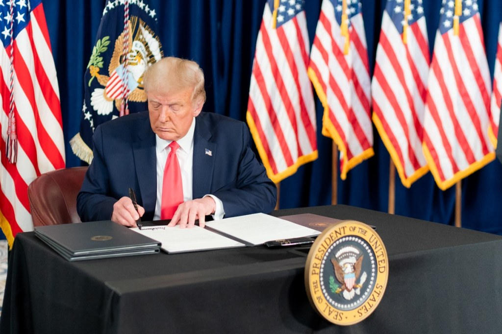 President Donald J. Trump signs a Presidential memorandum for continued student loan payment relief during the COVID-19 pandemic Saturday, Aug. 8, 2020, at a news conference in Bedminster, N.J.