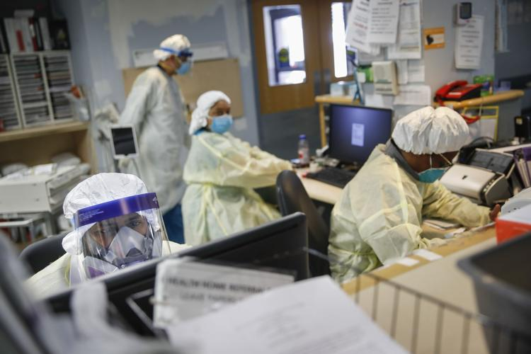 Emergency room doctors and nurses wear personal protective equipment while manning desks due to COVID-19 concerns at St. Joseph's Hospital, Monday, April 20, 2020, in Yonkers, N.Y.
