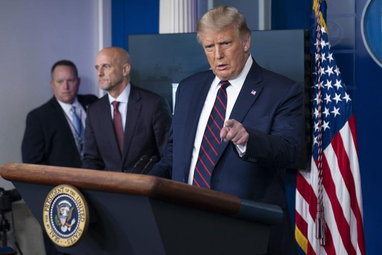President Donald Trump speaks, accompanied by Food and Drug Administration Commissioner Dr. Stephen Hahn, center, during a media briefing in the James Brady Briefing Room of the White House, Sunday, Aug. 23, 2020,