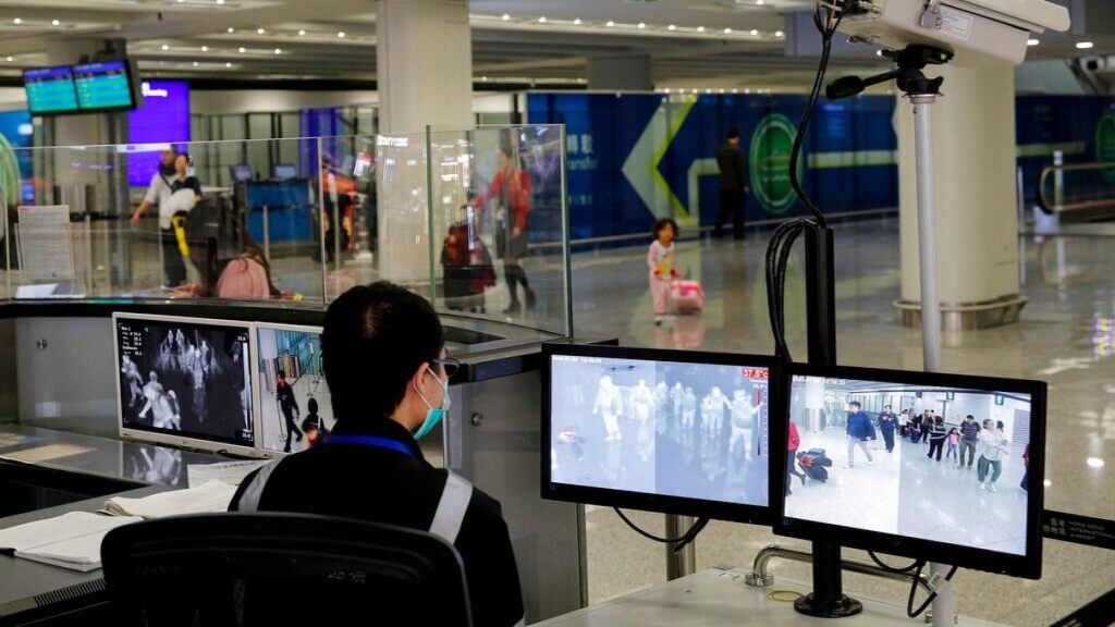 In this Jan. 4, 2020, file photo, a health surveillance officer monitors passengers arriving at the Hong Kong International airport in Hong Kong.
