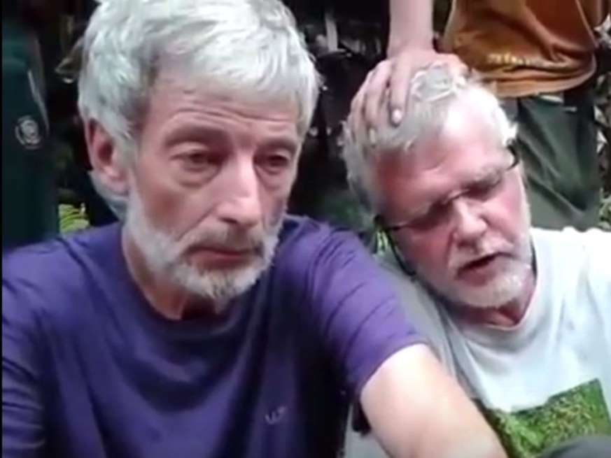 © YouTube Robert Hall, 50, (in purple on left) and John Ridsdel, 68, are seen in a hostage video.