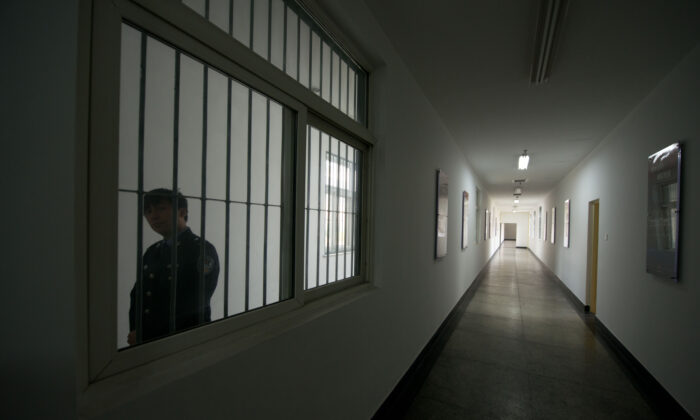 A guard looks through the window of a hallway inside the No.1 Detention Center during a government guided tour in Beijing, China on Oct. 25, 2012.